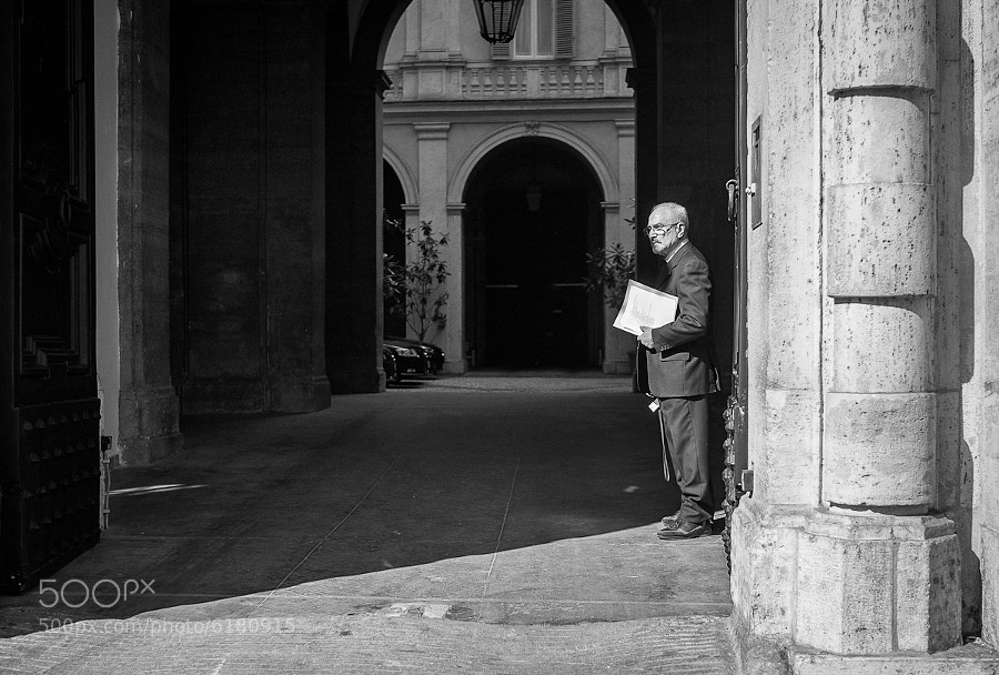 Man clutching important papers waits in the entrance to a Roman palazzo