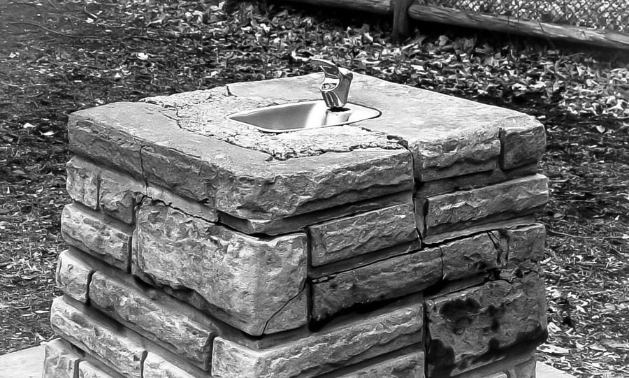 The old stone drinking fountain on my path to school still stands there today.
