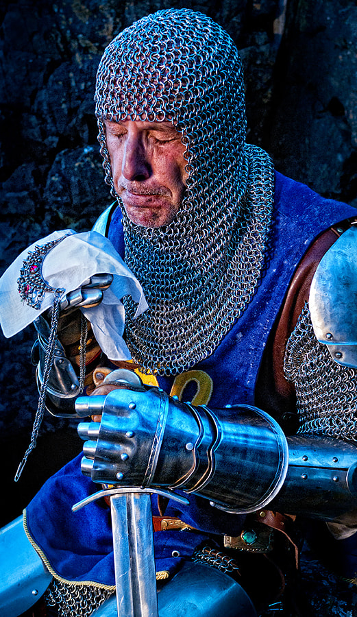 I just worked with a seasoned artists\' model, Michael Ward. He models professionally for about 30 years with countless fine artists - photographers, sculptors and painters alike. Shooting with him was a real treat, and I was excited he agreed to model for me in his fine armour from Britain. We also selected one of his swords - a fine and authentic Claymore blade. I spent a bit of time thinking ahead about the concept for the shoot. Surely, photographing a knight in armour asks for some mystical ambiance, a fairy tale like scenery and atmosphere like from William Waterhouse paintings. But, if I would go too much this direction and only this direction, it could be risky, touching of cheap and pretentious style. So, I decided to combine mystical feel of this shoot with real feelings and expressions - a human drama. How was it to be a warrior on his long battle path centuries ago? How many horrors hardened his soul, how many tragedies and lost comrades made him weep when nobody was watching? How about physical pain? I hope this image talks. Do you think so? Thank you for looking.