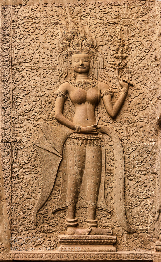 An Apsara is a female spirit of the clouds and waters in Hindu and Buddhist mythology. Apsaras are beautiful, supernatural female beings. They are youthful and elegant, and superb in the art of dancing. They are often the wives of the Gandharvas, the court musicians of Indra. They dance to the music made by the Gandharvas, usually in the palaces of the gods, entertain and sometimes seduce gods and men.  Apsaras represent an important motif in the stone bas-reliefs of the Angkorian temples in Cambodia (8th–13th centuries AD)