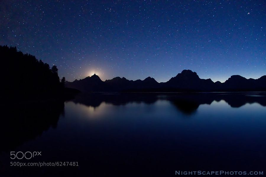 """I caught the last piece of the setting moon as it disappeared behind the Grand Teton peak  in Grand Teton National Park. The sun had set 90 minutes earlier behind the Teton Range, so there was still enough twilight to silhouette and reflect them in Jackson Lake. The brightest stars are still able to compete with the setting moon in this unique evening NightScape.  Virtually all my NightScapes are ONE exposure (less than 30 seconds), and with very little Photoshop correction. For more how-to and behind the scenes information, visit my <a href=""""http://intothenightphoto.blogspot.com/"""">Into The Night Photography</a> blog. For Milky Way photography workshops, visit my <a href=""""http://intothenightphoto.blogspot.com/2013/11/royce-bairs-2014-photography-workshop.html"""">NightScape Events</a> page. You can <a href=""""http://roycebair.smugmug.com/Personal-Work/Nightscapes/"""">order PRINTS here</a>."""
