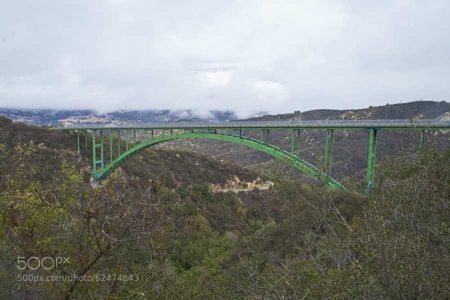 The Cold Spring Canyon Arch Bridge in the Santa Ynez Mountains links Santa Barbara, California with Santa Ynez, California. The bridge is signed as part of State Route 154. The current bridge was completed and opened to traffic in 1963 and won awards for engineering, design and beauty.