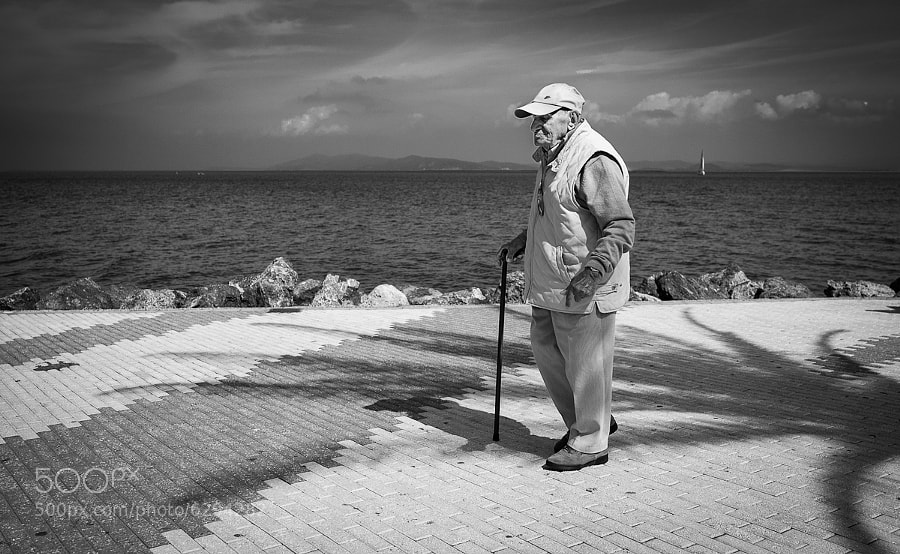 Elderly man enjoys a seaside promenade