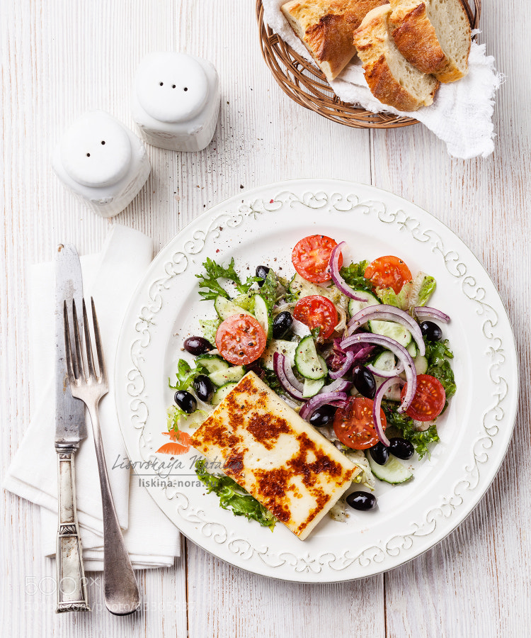 Fresh vegetable salad with grilled cheese on white wooden background