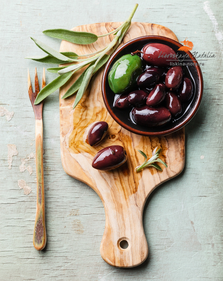 Olives with sage leaves on wooden background