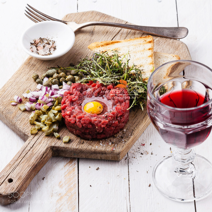 Beef tartare with capers and fresh onion on board with wine