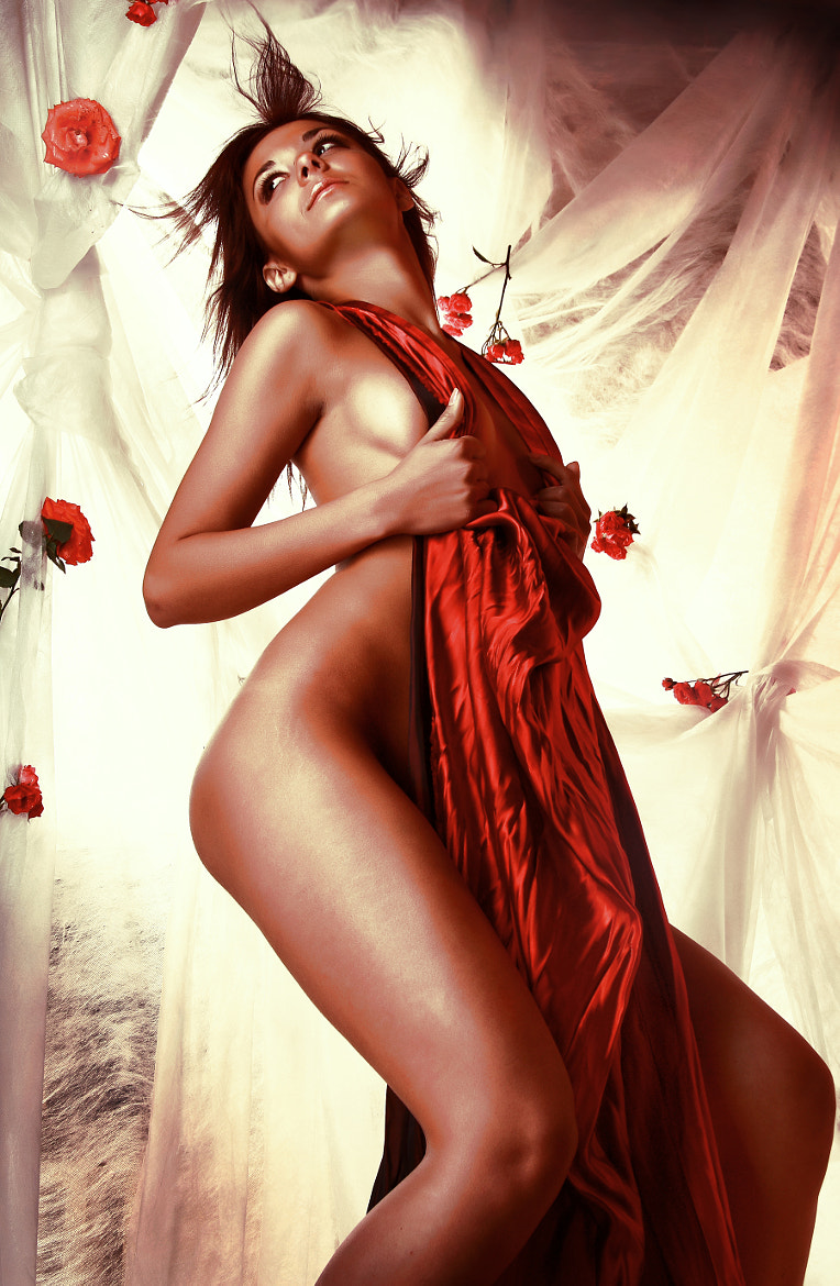 Photograph Sexual brunette in red dress. Flying petals of roses on backgrou by Sergey Petrosov on 500px
