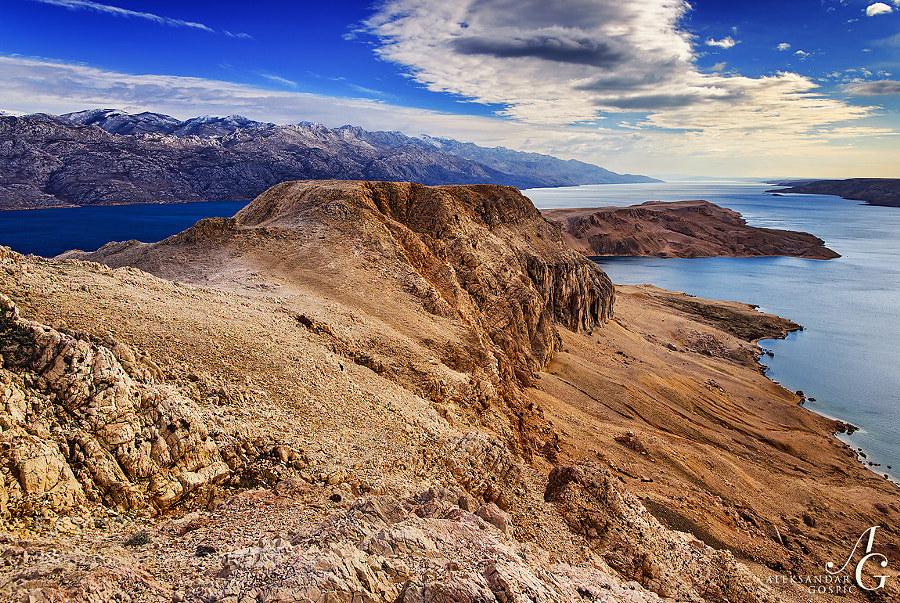 Incredible scenery of Pag island's hills, barren by the Bura wind, coming from the Velebit mountain, seen on the left, and the clouds of salt it picks up from the Velebit channel