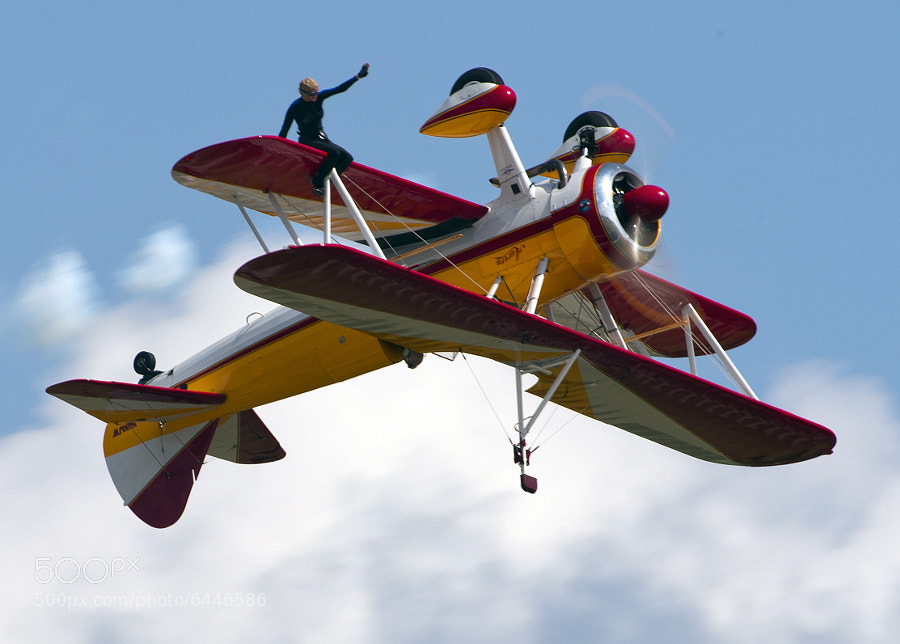 Jane Wicker sits on the inverted wing of her Stearman airplane