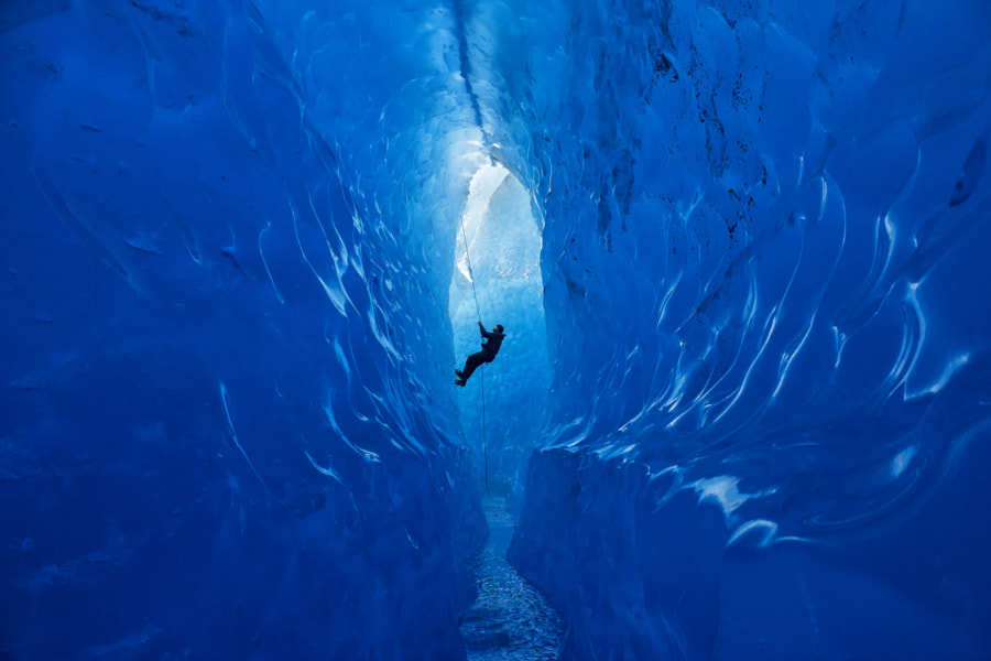 Climber Rappelling Into Cave by Jared Carlson on 500px.com