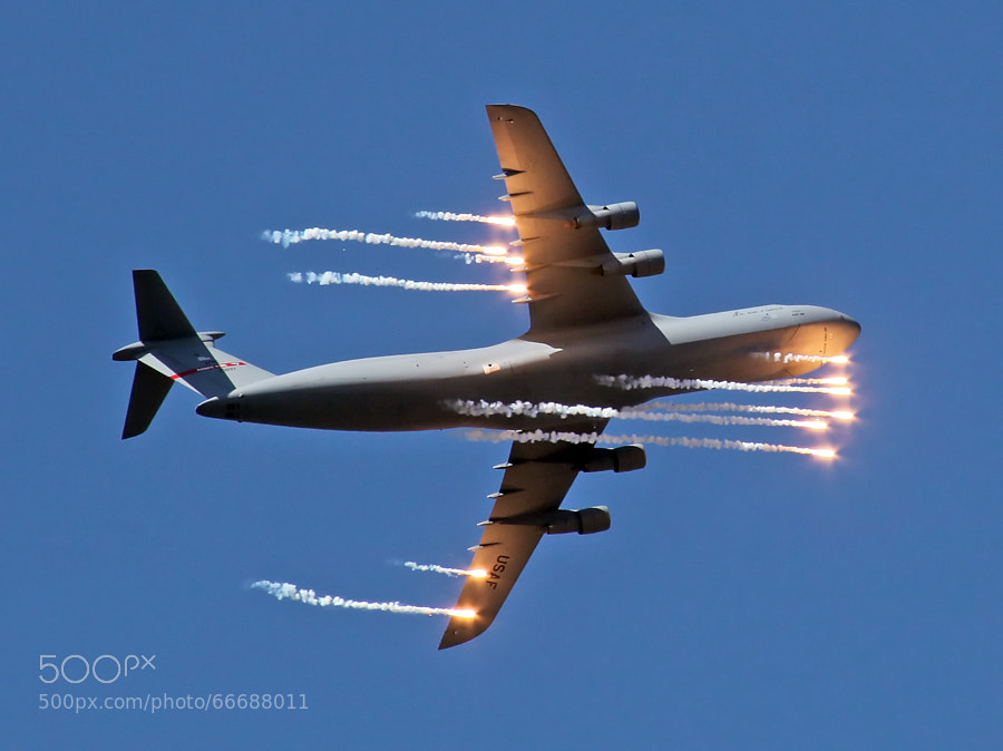 A C-5 Galaxy deploys flares to distract heat seeking SAMs, Surface to Air Missiles.
