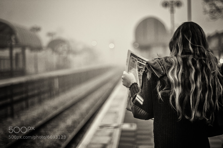 Woman reading newspaper in railway station