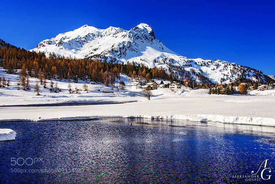 The first signs of liquid water in the still almost completely frozen and snow-covered lake Sils (1800m) in the Engadin valley. In the background is the Cima Murtaira (2858m).