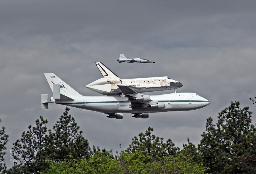 Space Shuttle Discovery makes a low pass in front of the National Air and Space Museum, Dulles International Airport prior to landing there.  Note the T-38 Talon chase/camera ship along side.