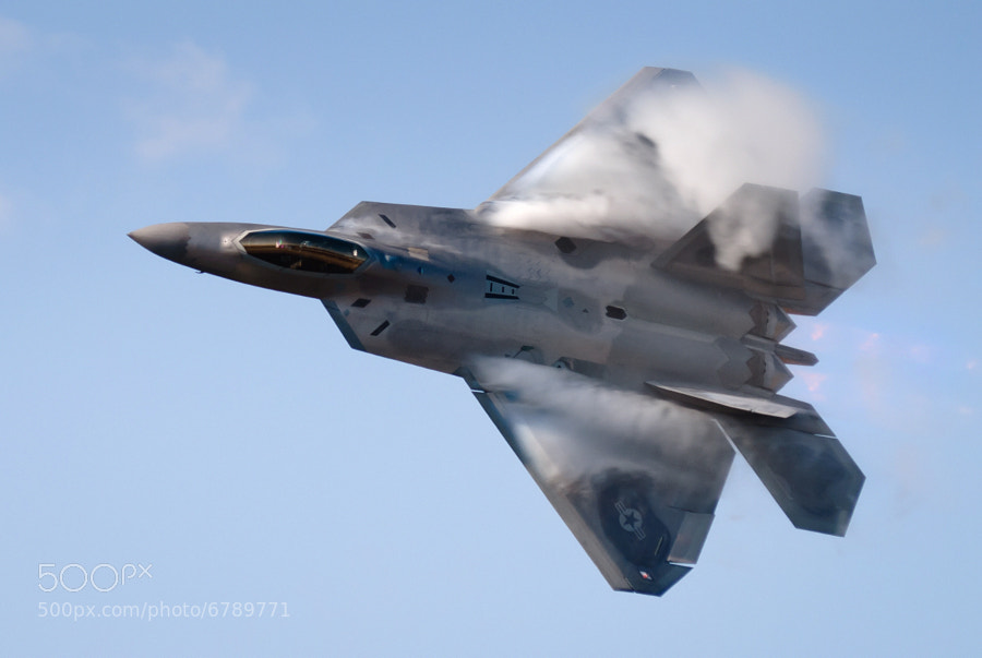 "Vapor pours off the wings of the F-22 as Maj Paul ""Max"" Moga brings the Raptor around for a photo pass during a morning practice session at Dobbins AFB"