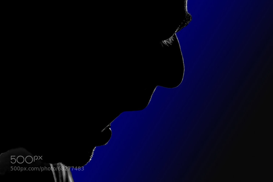 Silhouette of the profile of a man talking and in action showing the tip of his tongue popping out !!!