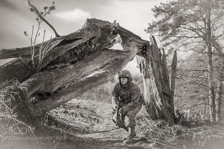 A German Sniper moves carefully along uneven terrain to scout an enemy position.
