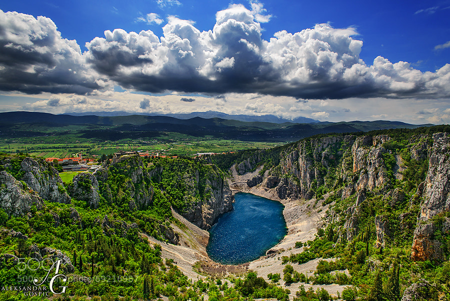 Cumulus luxuriate into the sky above Biokovo mountain, while Modro jezero (Blue Lake) in Imotski town is still catching a little bit of sunshine before the arrival of the new cyclone