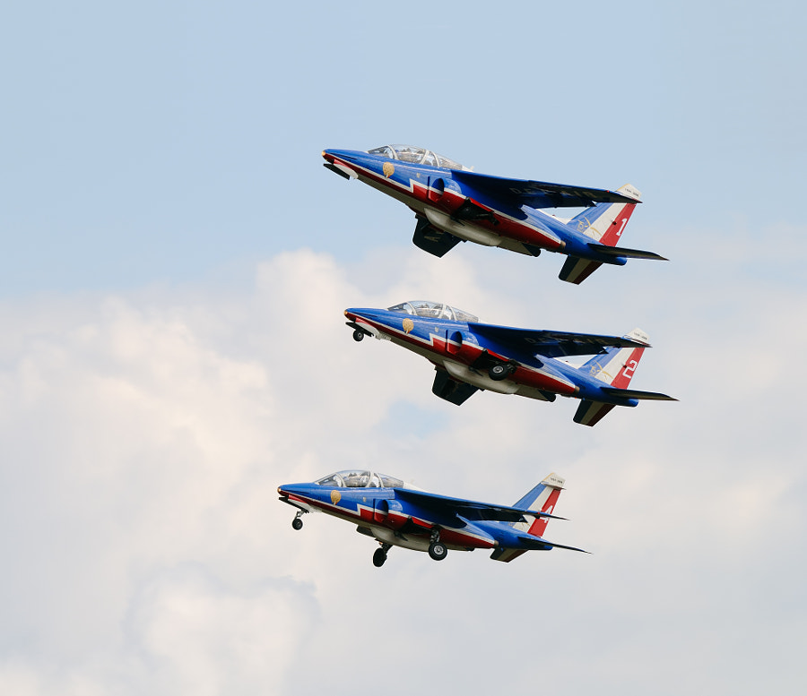 Three Alpha Jets of the Patrouille de France a little moment after their take off. What I personally like in this image are the three different stages in which the landing gear is shown. Shot taken during a Military Airshow on Volkel Air Base in the Netherlands.  Regards and have a nice day,  Harry