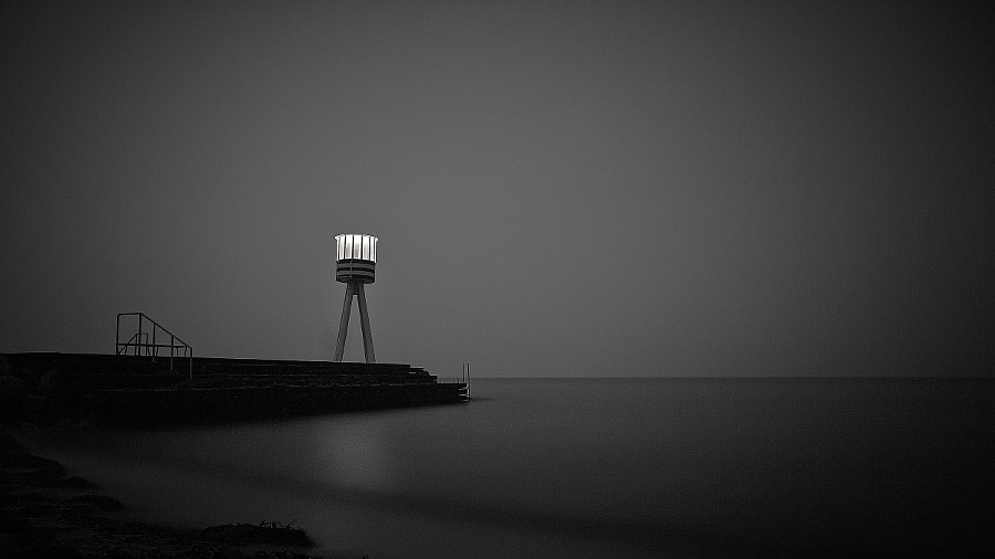 Old lifeguard tower at Bellevue Beach, Copenhagen Designed by the famous Danish Architect, Arne Jacobsen.  You can see some shadows of people walking on the jetty during the long exposure.