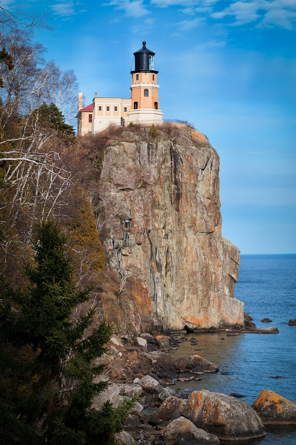 Split Rock Lighthouse is located southwest of Silver Bay, Minnesota, USA on the North Shore of Lake Superior. The structure was completed in 1910 by the United States Lighthouse Service at a cost of $75,000. It was built in response to the loss of ships during the famous Mataafa Storm of 1905, in which 29 ships were lost on Lake Superior. One of these shipwrecks, the Madeira, is located just north of the lighthouse. The light was first lit on July 31, 1910.</p>  <p>It is built on a 130-foot (40 m) sheer cliff. When completed, the lighthouse was lighted with an incandescent oil vapor lamp that burned kerosene. In 1940, the station was electrified and the lamp was replaced with a 1000 watt electric bulb. <br />   <br />The light was retired in 1969 by the U. S. Coast Guard. The lighthouse is now part of the Split Rock Lighthouse State Park and is operated by the Minnesota Historical Society. The site includes the original tower and lens, the fog signal building, the oil house, and the three keepers' houses. It is restored to appear as it did in the late 1920s. The site was added to the National Register of Historic Places in 1969. On June 30, 2011, the lighthouse was designated as a National Historic Landmark.