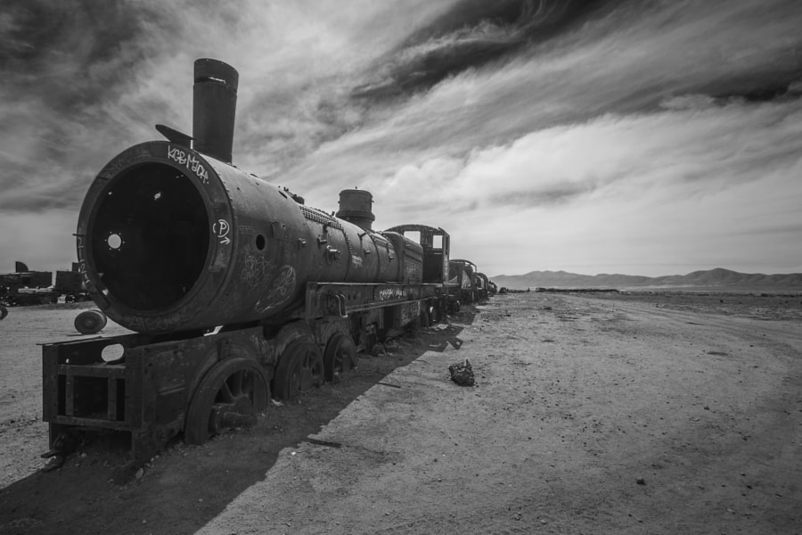 'Cementerio de trenes', the antique train cemetary, 3 kilometers (1.9 miles) outside the Uyuni city. From the end of the 19th century till this day, Uyuni has been an important transportation hub for trains. The rail lines, constructed between 1888 and 1892, were built by British engineers who were invited by the British-sponsored Antofagasta and Bolivia Railway Companies. For the next decades the trains were used for carrying minerals from the Andes mountains to the Pacific Ocean ports.  During the 1940's the mining industry collapsed, partly because of mineral deplation. Many trains were abandoned outside Uyuni, forming this mass train cemetary. The train cars and locomotives, many of them dating back to the early 20th century, are now rusted and eroded by the salt winds blowing over Uyuni. Many pieces of metal have been stolen as there is no fence or guards.