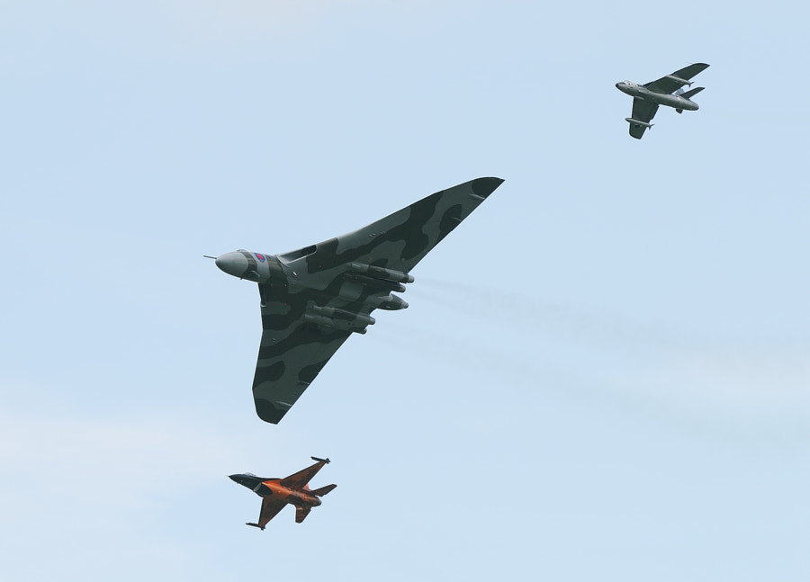 During a heritage flight at Volkel Air Base these two alongside of this mighty Avro Vulcan V bomber really look like toy planes. At the left wing, your right hand side, you see a Hawker Hunter F6A and on the right wing a Dutch F16.  Regards and have a nice day,  Harry