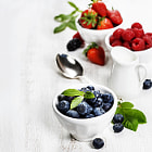 Постер, плакат: Berries in bowls on Wooden Background