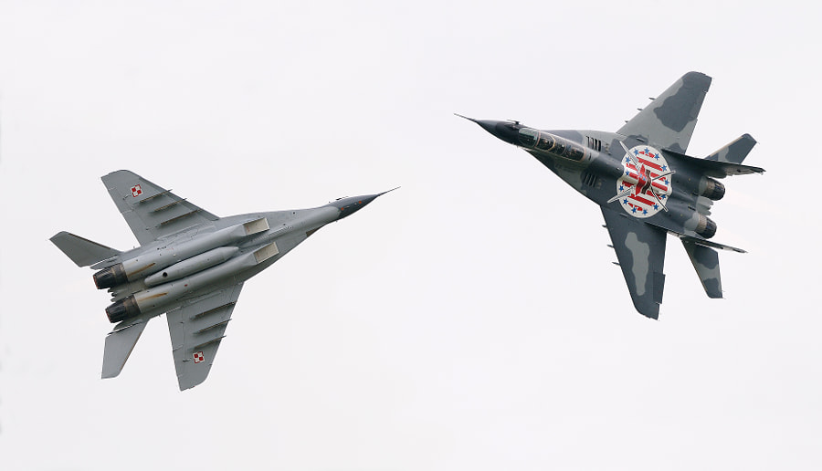 """Two different shots combined to one giving you a good view of both sides of this MiG 29 Fulcrum.  The Mikoyan MiG-29 (Russian: Микоян МиГ-29; NATO reporting name: """"Fulcrum"""") is a fourth-generation jet fighter aircraft designed in the Soviet Union. Developed by the Mikoyan design bureau as an air superiority fighter during the 1970s, the MiG-29, along with the larger Sukhoi Su-27, was developed to counter new American fighters such as the McDonnell Douglas F-15 Eagle, and the General Dynamics F-16 Fighting Falcon.[6] The MiG-29 entered service with the Soviet Air Force in 1983.  While originally oriented towards combat against any enemy aircraft, many MiG-29s have been furnished as multirole fighters capable of performing a number of different operations, and are commonly outfitted to use a range of air-to-surface armaments and precision munitions. The MiG-29 has been manufactured in several major variants, including the multirole Mikoyan MiG-29M and the navalised Mikoyan MiG-29K; the most advanced member of the family to date is the Mikoyan MiG-35. Later models frequently feature improved engines, glass cockpits with HOTAS-compatible flight controls, modern radar and IRST sensors, considerably increased fuel capacity; some aircraft have also been equipped for aerial refuelling.  Following the dissolution of the Soviet Union, a number of successor states have continued to operate the MiG-29; the largest of which is the Russian Air Force. The Russian Air Force wanted to upgrade its existing fleet to the modernised MiG-29SMT configuration, but financial difficulties have limited deliveries. The MiG-29 has also been a popular export aircraft; more than 30 nations either operate or have operated the aircraft to date, India being one of the largest export operators of the type. As of 2013, the MiG-29 is in production by Mikoyan, a subsidiary of United Aircraft Corporation (UAC) since 2006.  Best wishes and have a nice day,  Harry"""