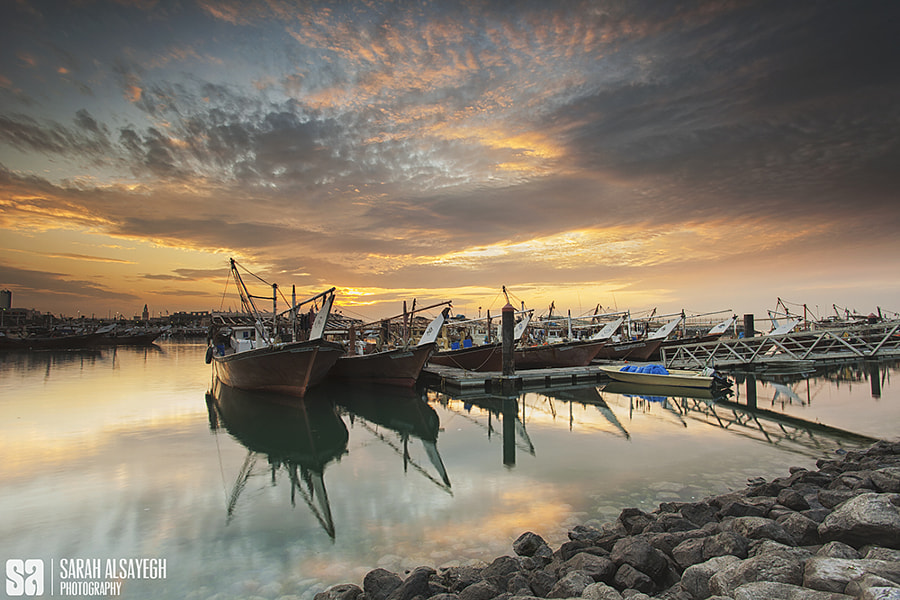 Fine Art Landscape Photography Sunset Reflection Over Sharg Fishing Boats by landscape and nature photographer Sarah Alsayegh