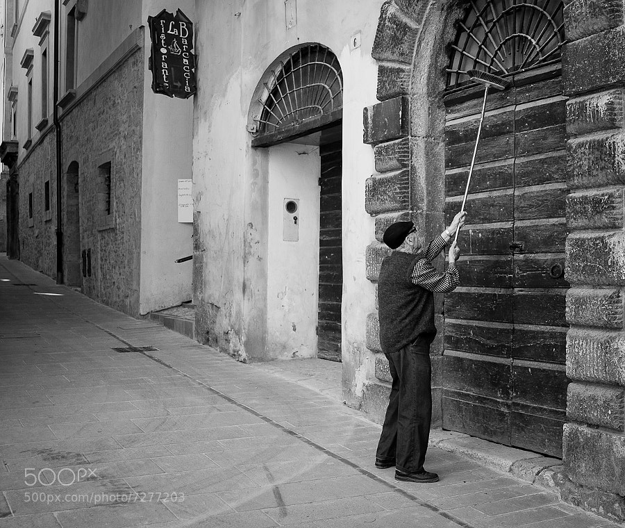 Man gives his front door a good clean in Italian street