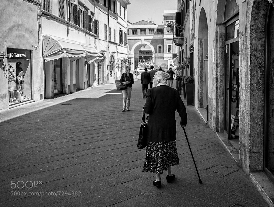 Elderly woman walks slowly towards the Friday morning market in an Italian town