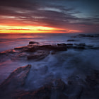 A scene from an amazing morning at Narrabeen in the autumn of 2012.  The water takes on a misty blue appearance as the rich red and orange sky of an imminent sunrise lights the jagged rocks on the rock shelf.