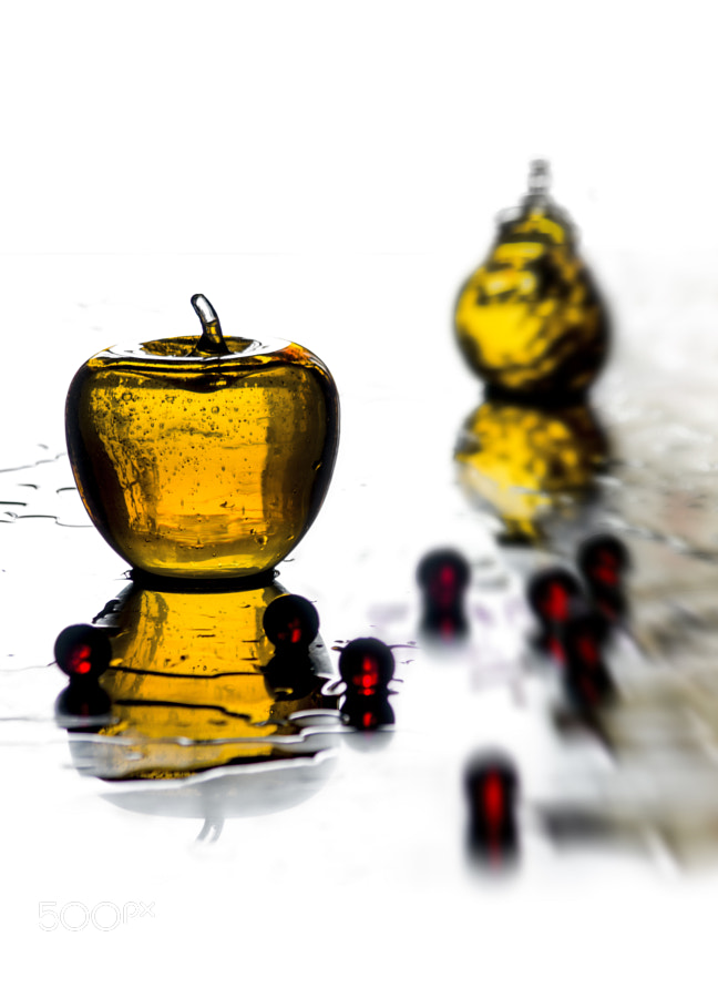 yellow glass apple and pear with red marble on a green marble table captured against light