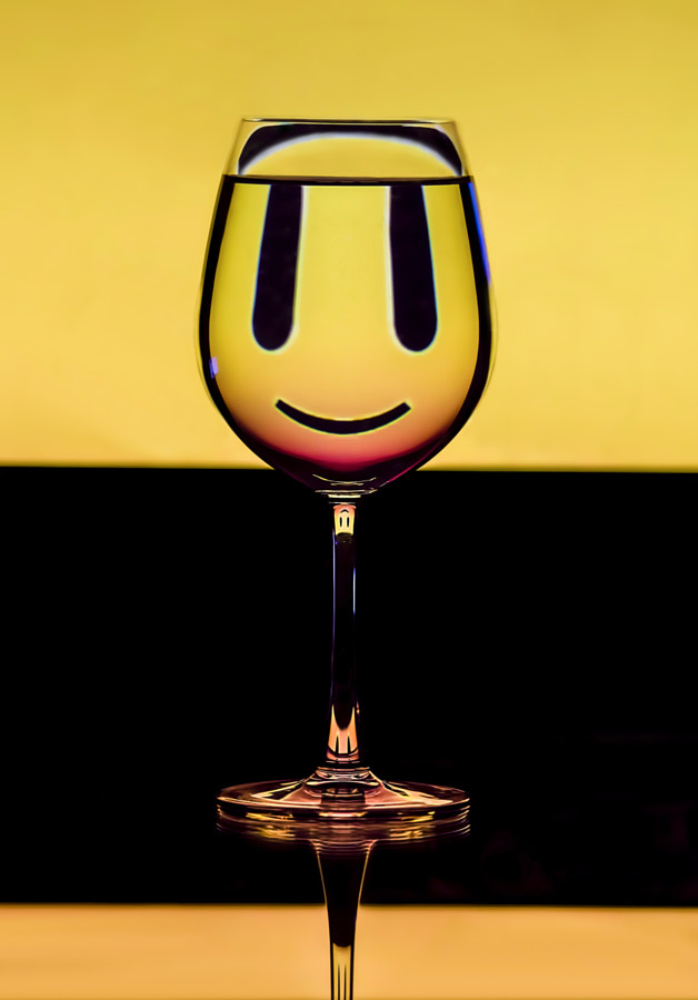 a glass filled with water refracting inversed smiley in the monitor