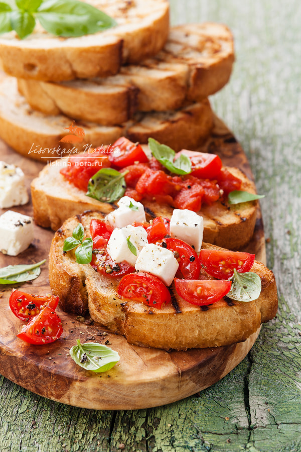 Italian bruschetta with chopped tomatoes, basil and cheese on grilled crusty bread
