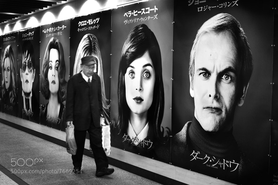 Street photo of a man walking against movie poster as backdrop