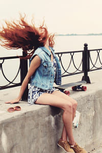 Toned image of young women sitting with skateboard on parapet and shake her hair by Heather Balmain on 500px