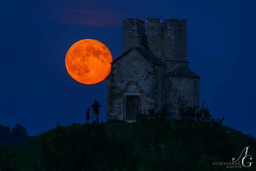 Bloody Super Moon rises tonight above the horizon beside the church St. Nicholas near Nin