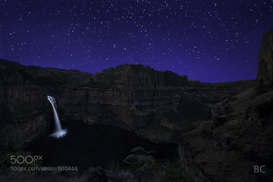 This is Palouse Falls State Park in Washington.   This picture is the culmination of many months of anticipation! I visited this place early in the summer and immediately wondered what would it be like with stars? It wasn't until later in the fall I could finally make the trip out here to try.   I've got another shot from down at water level looking up that I'll post in the future, but for now, this one is more my favorite. This is ironic because this shot was done on my way up and out and only as an afterthought. I'm always amazed at which shots from the night turn out to be the keeper and which ones don't.   This night was an exciting adventure for me. Navigating the trail down into the bottom at night was nerve racking! Then, being inside and looking up at the sheer walls with the stars overhead and Milky Way coming up and out- it really was incredible. Certainly a special experience.   I have a long, drawn out story from this trip on a wordpress blog, but I think I'll put it on the blog over here at 500px to see if you guys like reading stories.   Thanks for the visit!  I put up a blog with the long version of the story here on 500px: http://500px.com/BenCanales/blog/4531