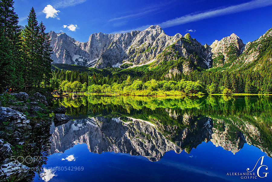 Mighty north wall of Mangart (2678m) reflects in the Upper Lago di Fusine lake during the tranquil morning in the Italian part of Julian Alps