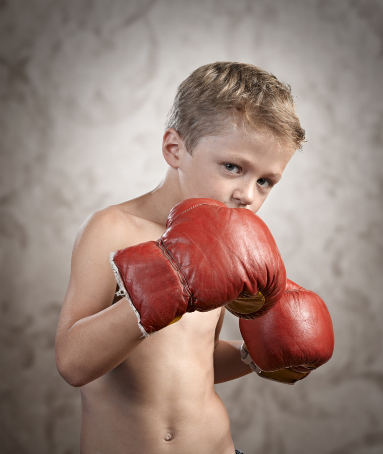 Non Aggressive child wearing boxing gloves on textured backgroun by Bombaert Patrick on 500px.com