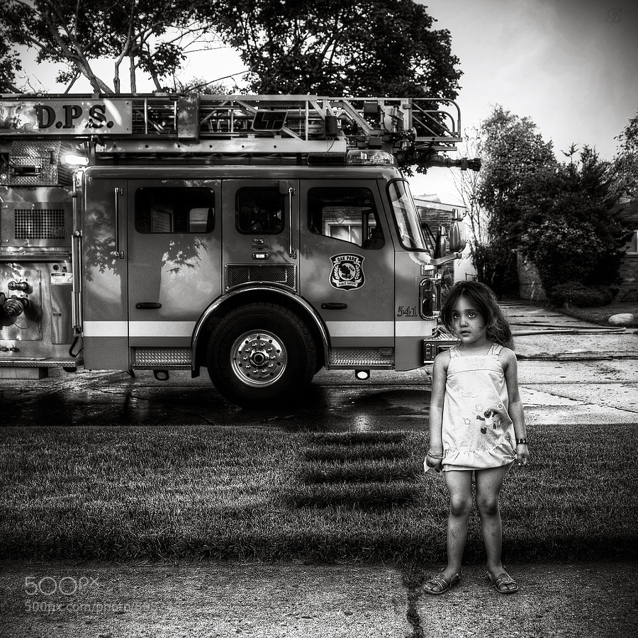 a young child watches as firefighters battle a blaze