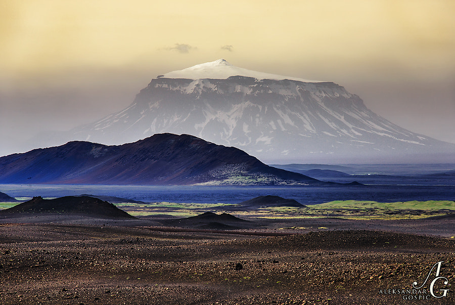 In the middle of the central volcanic highlands of Iceland and desert Odađahraun rises Herđubreiđ (1692m) volcano, here seen 40km away through a veil of dust storm that was raised by strong southerly wind more than 1000m high into the air