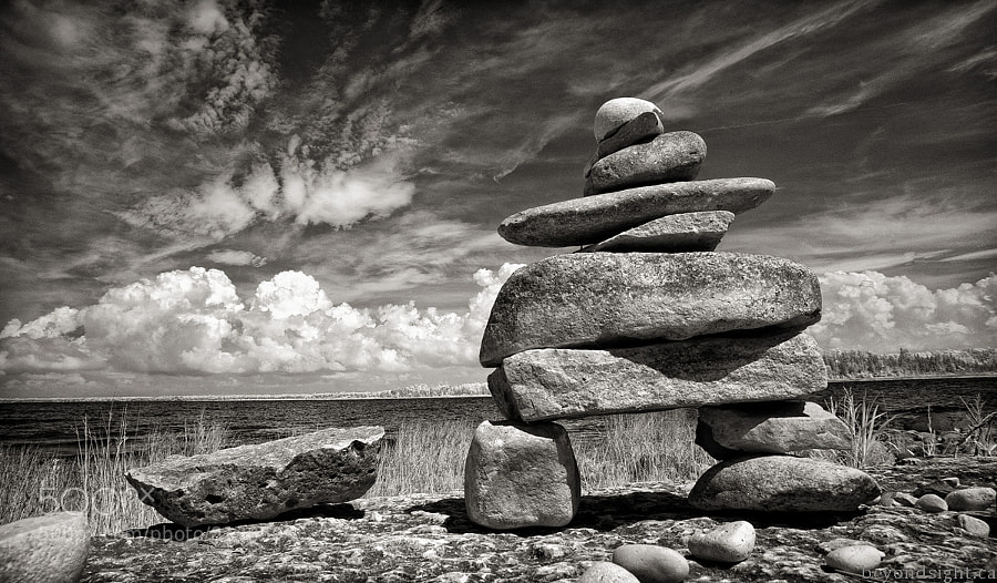 A Inukshuk stands by the shores of Lake Huron in Macgregor Point Provincial Park.   Infrared image.
