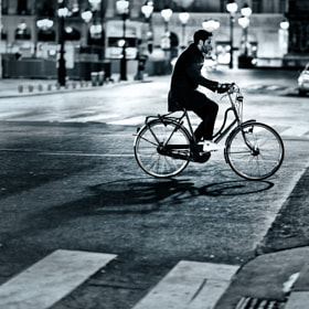 Bicyclist crossing an intersection at Place Vendôme, Paris, France