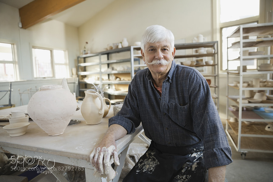 Photograph Portrait of man at pottery studio by Hero Images  on 500px
