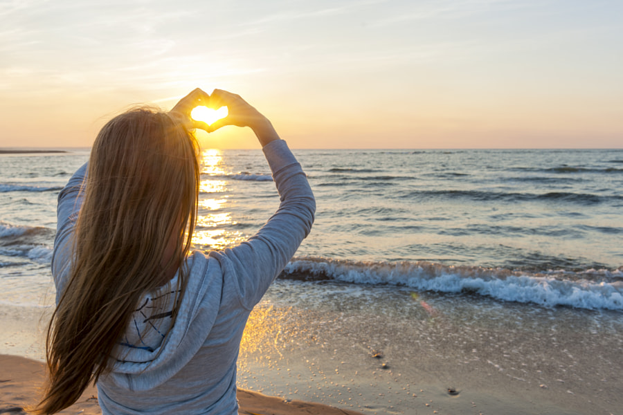 Girl holding hands in heart shape at beach by Elena Elisseeva on 500px.com