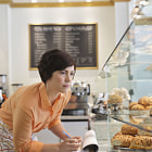 Постер, плакат: Female small business owner taking inventory in coffee shop