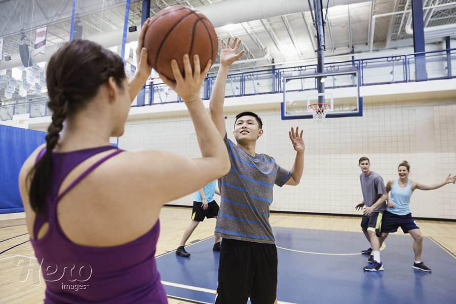 Men and women playing basketball in gym